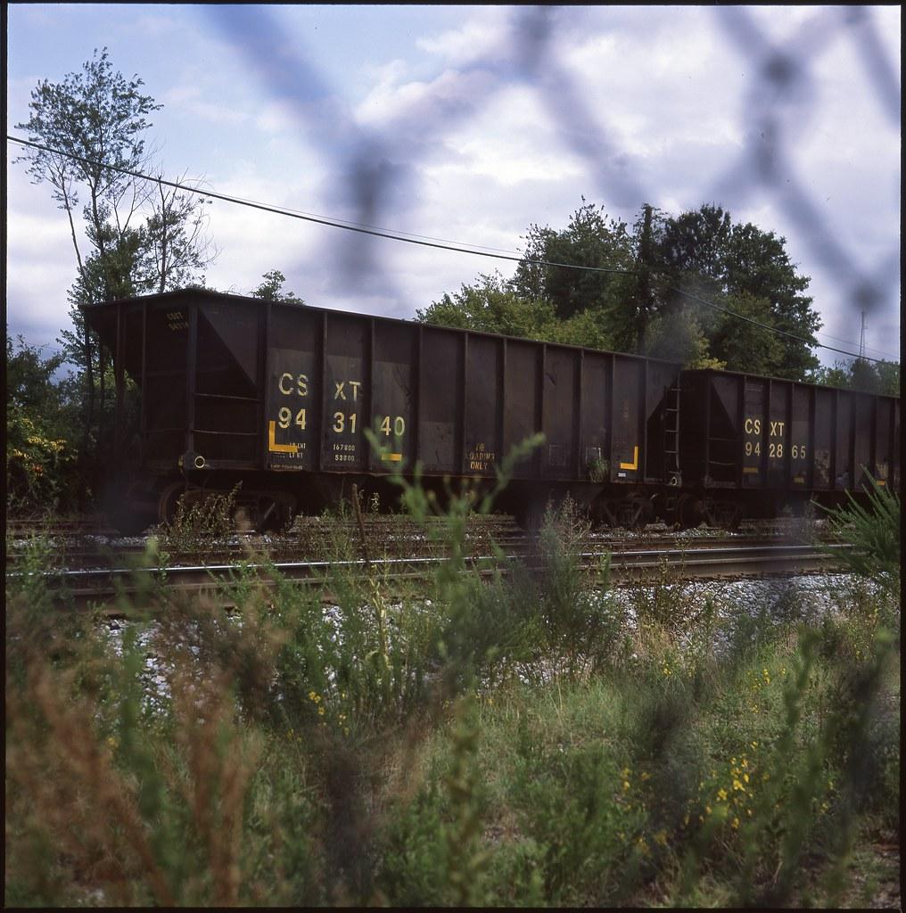 train cars as seen through a chainlink fence