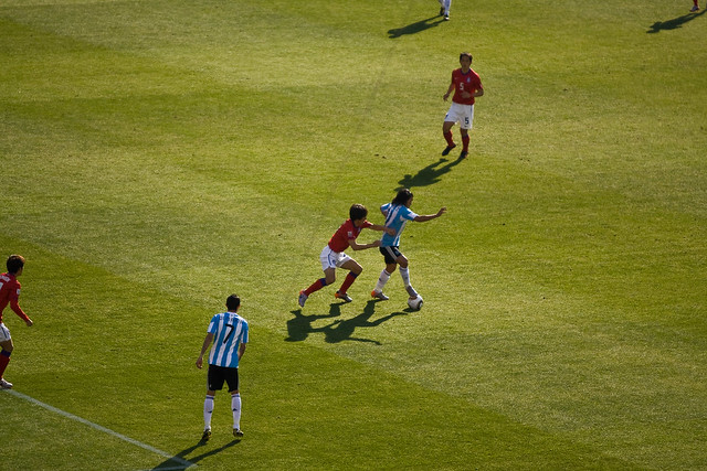Tevez attempts to shake off a defender