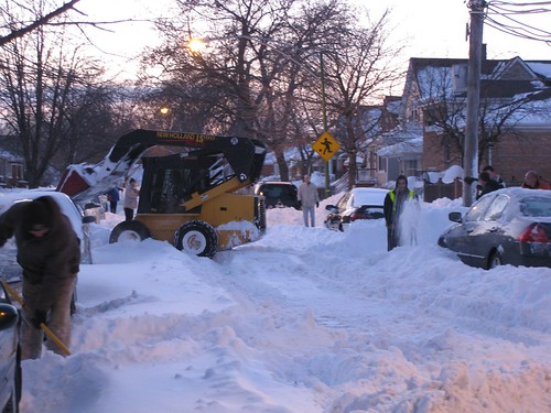 People with shovels, snowblowers, and a frontend loader