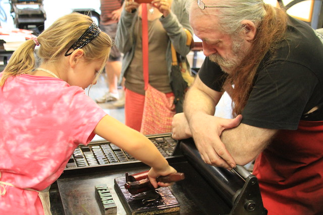 Girl printing in the Gutenberg Museum Print Shop