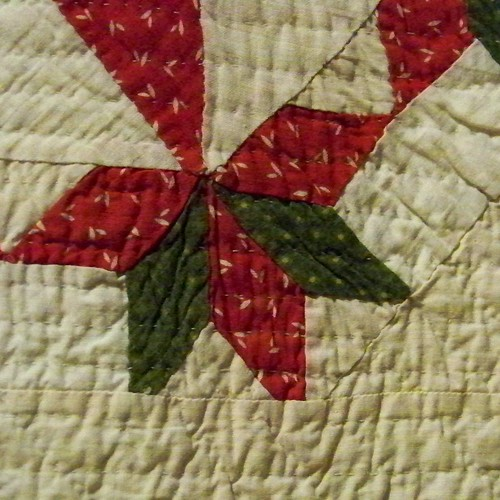 detail of antique quilt: red and green star with cut off points