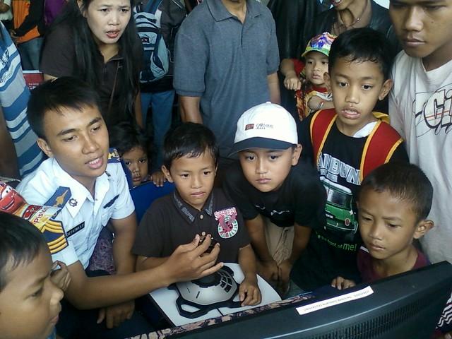 Didampingi mahasiswa Universitas Nurtanio Bandung, seorang anak sedang mencoba menerbangkan pesawatnya. (Foto: Yudha PS)