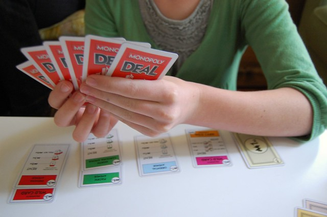 "A person holding a hand of ""Monopoly Deal"" cards."