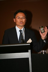 Hiro Fujimori demonstrating a portable talking book player from PLEXTALK.  Photo taken by Grant Hutchings.