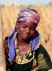 West African girl daily pounds grain for her f...