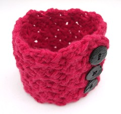 Crochet wrist cuff with shiny black shell buttons