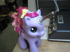 A purple My Little Pony figurine with a fuchsia mane. A soldering iron emerges from its forehead, pointing just to the right of the camera.