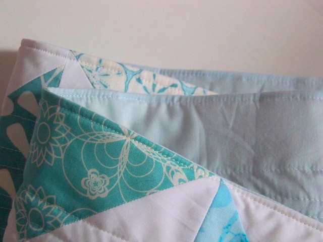 folded aqua and white quilted table runner