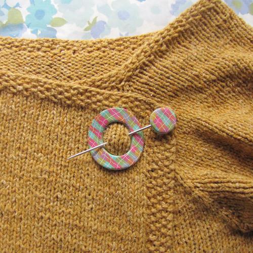 Plaid polymer shawl pin on handknit sweater