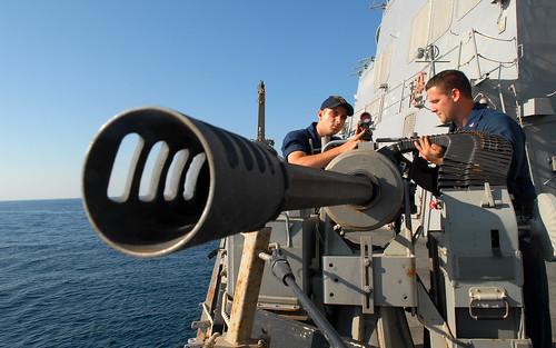 Navy gunner's mates inspect machine gun.
