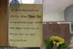 A handwritten sign hangs on the window that separates the front of the store from the pharmacy in the back. There are many handwritten notes and signs throughout the rest of the store.