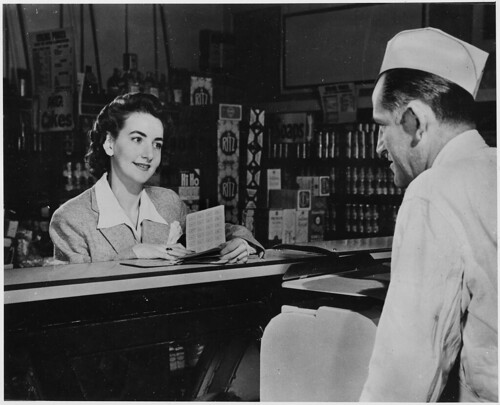 """A Customer Can Use the Ration Books of the Whole Family. But the First Thing She Will Want to Know When She Buys Pork Chops, Pound of Butter or a Half Pound of Cheese Is - """"How Many Points Will It Take?"""" 1941 - 1945"""