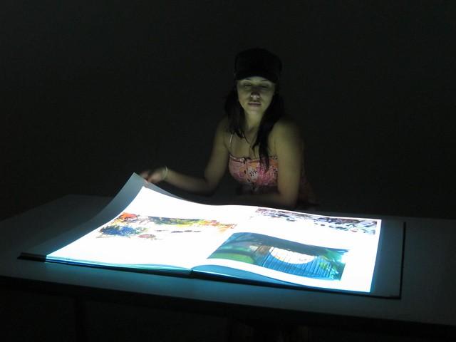 Carolina flips through illuminated pages
