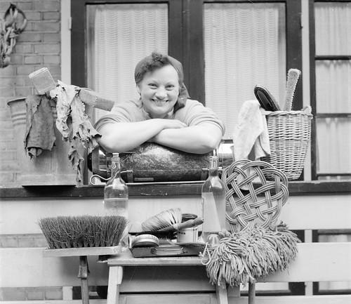 Huisvrouw met schoonmaakattributen / A housewife surrounded by cleaning utensils