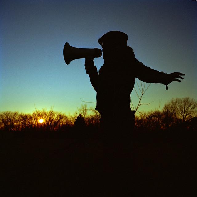 The bullhorn poet speaks to the horizon.