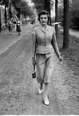A young woman walking with camera in hand