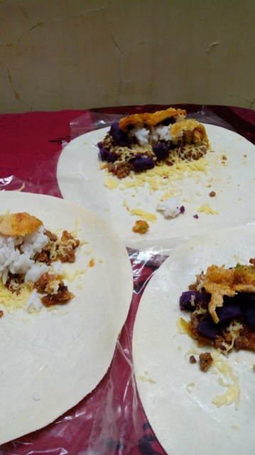 Tortilla dengan daging, keju, telur dadar, mantang ungu, dan nasi untuk membuat buritto