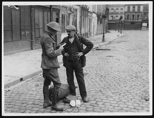 British Intelligence sergeant questioning a stranger in the deserted streets of a French town