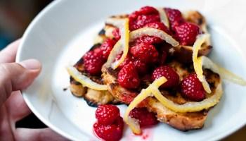Ontbijt met gebakken suikerbrood, frambozen en citroenschilletjes
