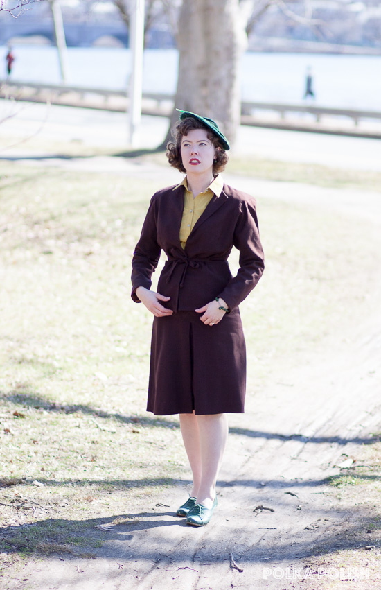1940s outfit with a brown suit, chartreuse blouse, and forest green tilt hat and shoes
