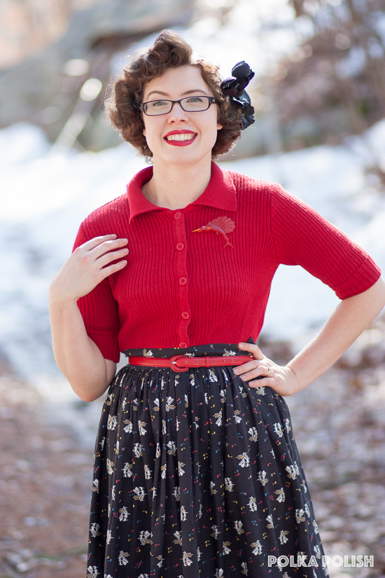 1950s inspired outfit featuring a red cardigan, and a black and white piano novelty print skirt
