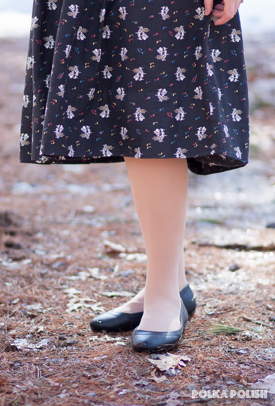 Crocs black flats paired with a vintage 1950s piano novelty print cotton skirt in white, black, yellow, and blue