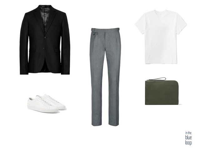 Look smart-casual masculino con pantalón de vestir gris, sneakers blancas, portafolio, camiseta blanca y blazer azul marino