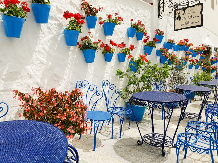 A terrace with blue chairs and tables, and blue flower pots on the wall
