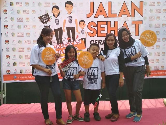 Salah satu keluarga peserta jalan sehat bergaya di photo booth yang disediakan KPU Tulungagung, Minggu (29/10)