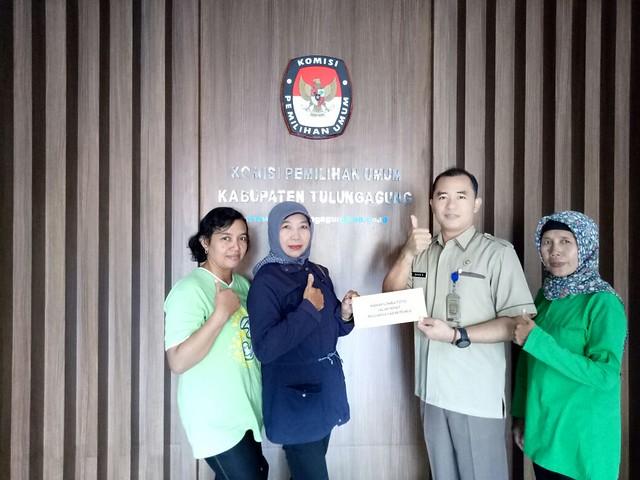 David Hartanto Kasubbag Teknis dan Hupmas KPU Tulungagung memberikan hadiah kepada komunitas srikandi sebagai salah satu pemenang foto kelurga sadar pilkada 2018 (13/12)