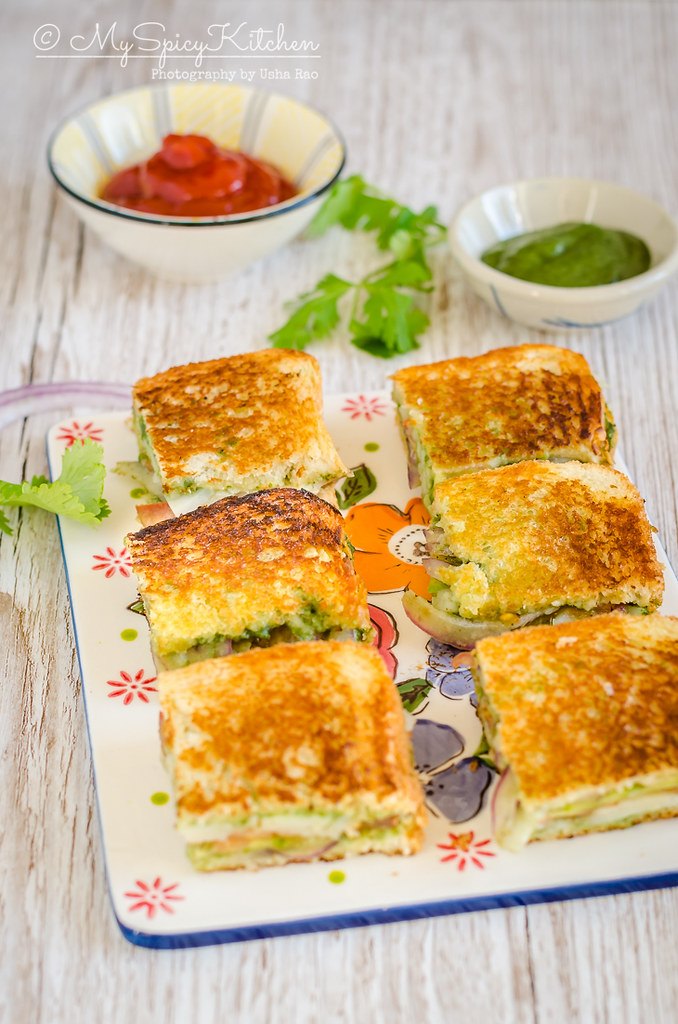 Bombay Grilled Vegetable Sandwich is a street food from Mumbai India.  Spicy green chutney is the spread and potato onion cucumber tomatoes are used to make the sandwich.