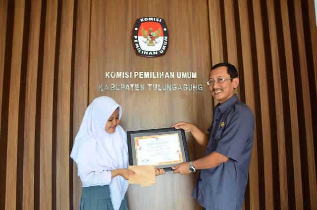 Sekretaris KPU Tulunggaung Drs. Mundiyar saat menyerahkan piagam penghargaan dan uang pembinaan kepada Nadin Aulia siswi kelas XII 5 jurusan MIPA SMAN 1 Kedungwaru di Kantor KPU Tulungagung