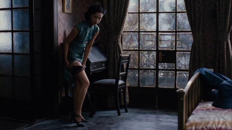 タン・ウェイが旗袍を捲ると、中からガーター・ストッキングが現れました。