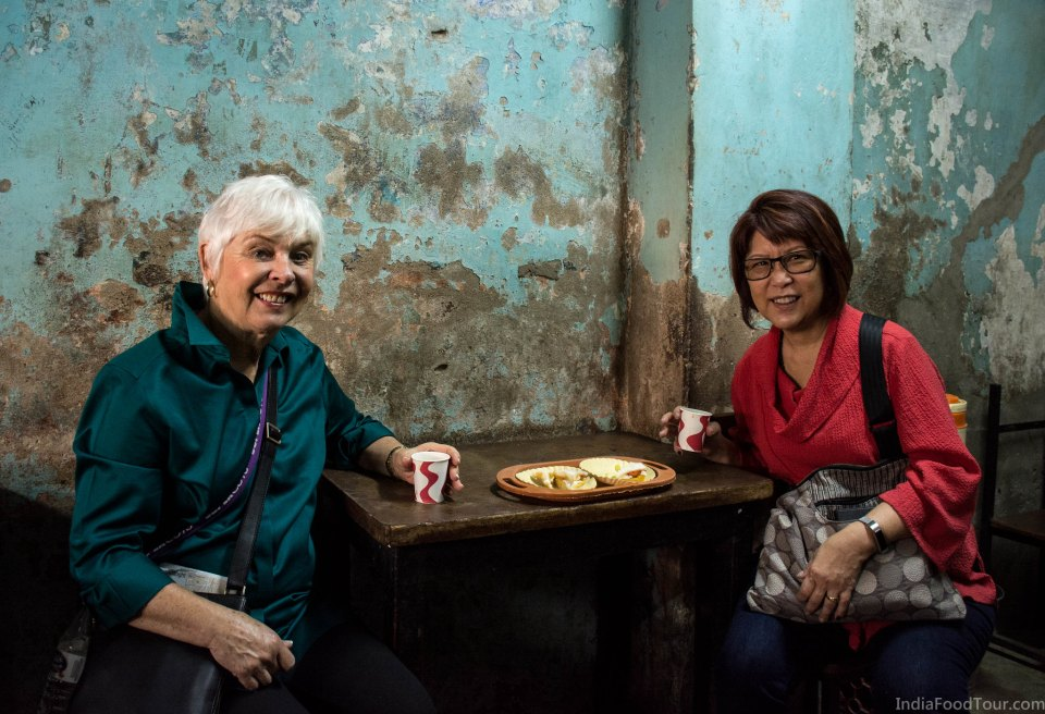 Tasting a fruit sandwich and masala chai during food walk in Old Delhi