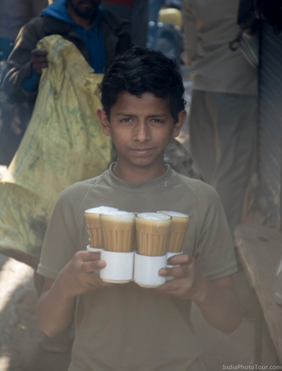 A boy in the street carrying tea