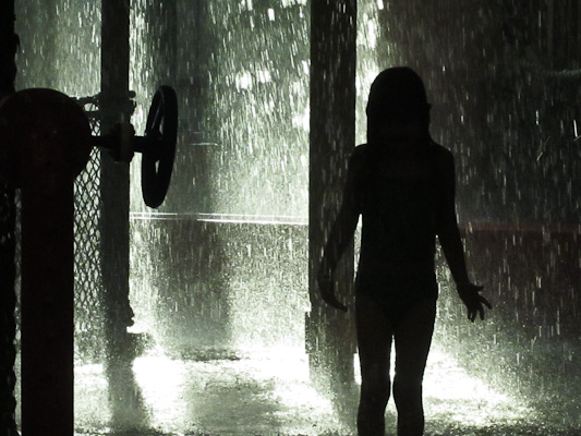 The little one silhoutted against falling water.