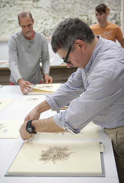 Mark Dion stamping prints at Graphicstudio