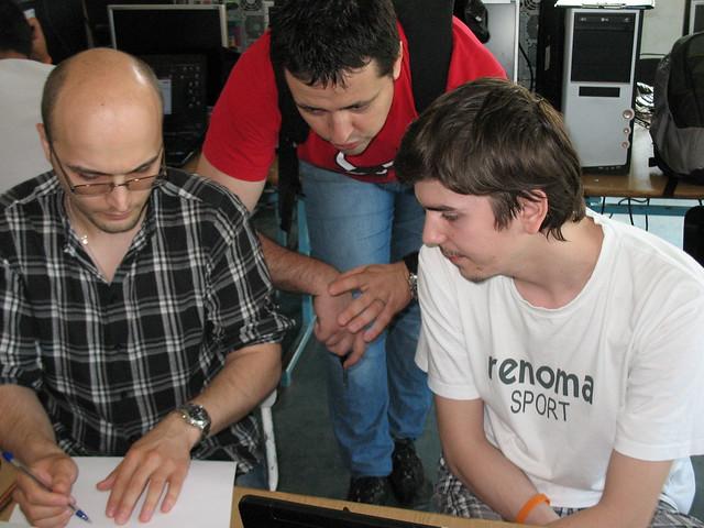 Studenții la master Dumitru Emciuc și Mihai Sterpu discutând cu unul dintre mentori: Marius Ursache (Grapefruit)