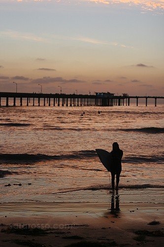 Lone surfer girl in Ocean Beach, San Diego, CA, USA