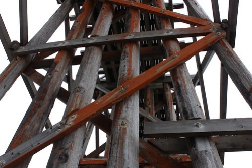 Red Trestles: The underside of a trestle bridge, shot from the ground looking up. The supporting posts are streaked with red algae.