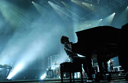 Kris Allen playing piano blue light on stage American Idol tour photo by Greg Barber Express