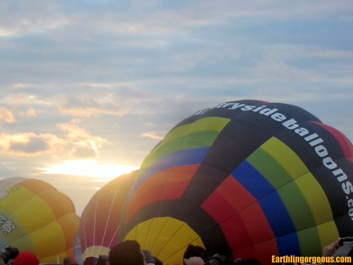 sunrise behind the inflating hot air balloons