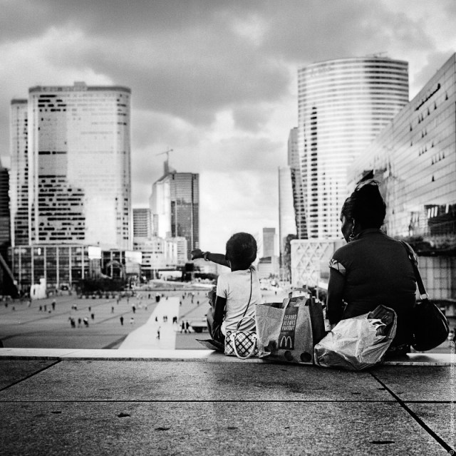 Woman and child having MacDo lunch while observing La Défense plaza, Paris