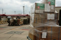 Boxes of aid waiting to be delivered by III MEF Marines