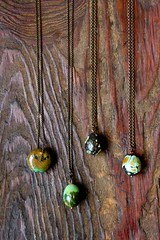 four chunks of turquoise on four brass chains