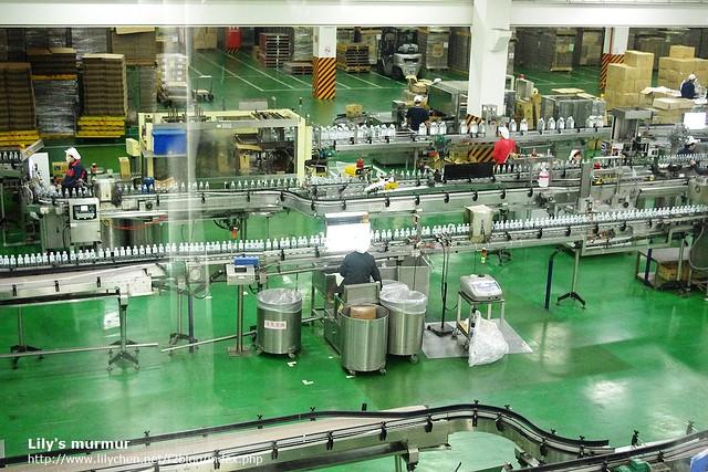 填充完畢的礦泉水正在進行人工檢驗,檢驗完就由機器自動裝箱。