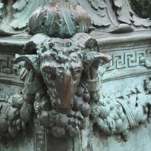 Detail of the cast bronze lamp post showing a close up of a ram's head