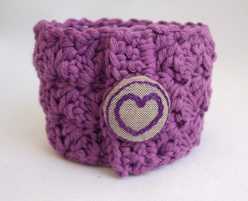 Crochet wrist cuff with hand embroidered button