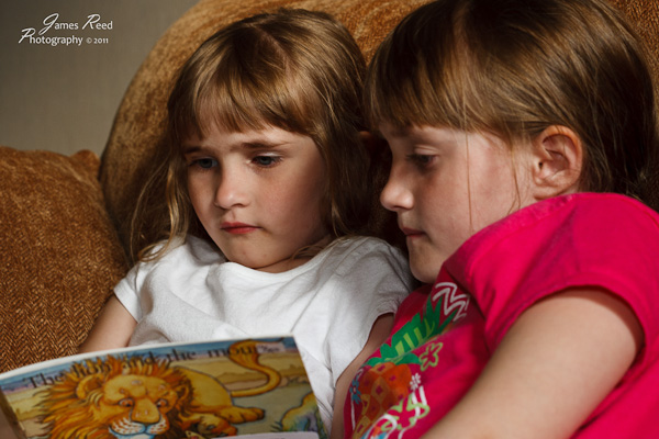 The big one helps the little one with her reading homework.