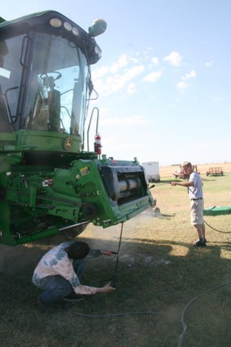 Adam and Adreas power wash off the combine.